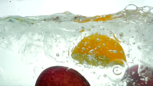 Lime orange apple and lemon drop in the ice water. Close up. Slow motion. video