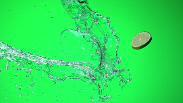 SLO MO Lime slice hitting a water splash on green background video