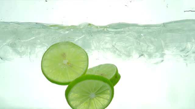 Lime slices drop in the ice water. Close up. Slow motion. video