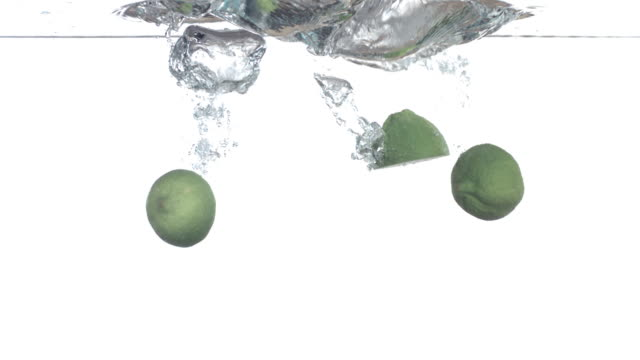 Limes splashing into water, slow motion video