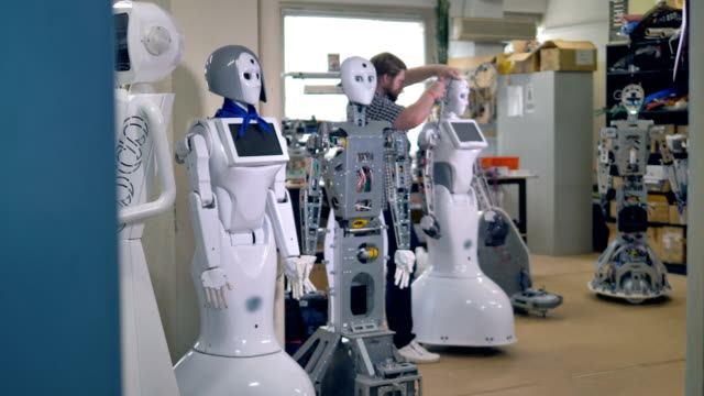 A line of tall robots await for a busy repairman to start fixing them. 4K. video