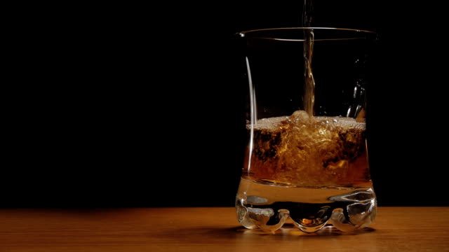 Liquor or whiskey poured in a glass against black background video