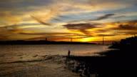 lisbon bridge 25 of april christ and Tajo river with sunset timelapse with people silhouette video