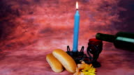 Lit Shabbath candles with uncovered challah bread video
