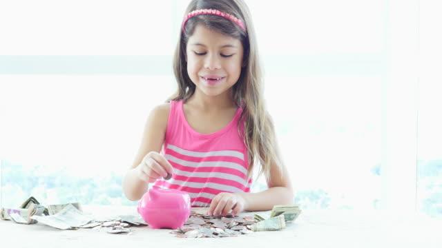 Littel girl puts coins into her piggybank video