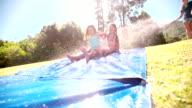 Littel girls sliding down a water slide happily video