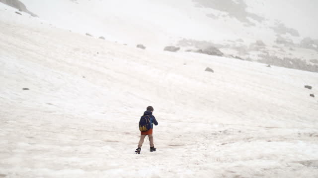 Little 6 years old boy with backpack hiking in High Snowy Mountains. He walk and waves video