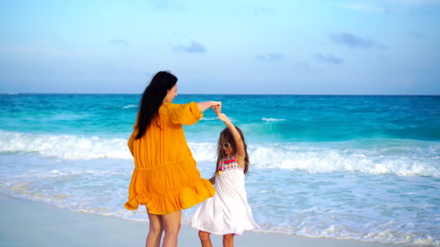 Little adorable girl and young mother at tropical beach in warm evening with beautiful sunset video