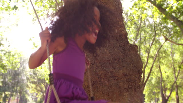 Little Afro girl happily playing on a swing in park video