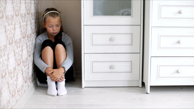 Little aggrieved girl sitting in the corner of a room hugging her knees video