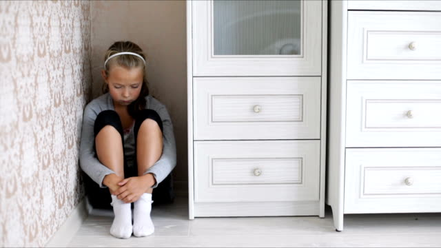 Little aggrieved girl sitting in the corner of a room on the floor hugging her knees video
