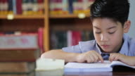 little asian boy bee bored with reading,library in thailand video