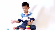 Little asian boy playing rainbow tower video
