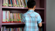 Little Asian child reading book in library video