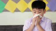 Little Asian child sick with flu sneezing and clean with tissue paper video