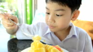 Little asian cute boy eating piece of ripe pineapple . video