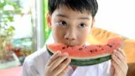Little asian cute boy eats ripe watermelon  . video