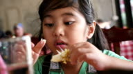 Little Asian girl enjoy eating with seafood meal, Pan shot video
