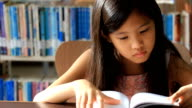 Little Asian girl reading a book in library video