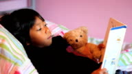 Little Asian Girl Reads Story Book To Teddy Bear video