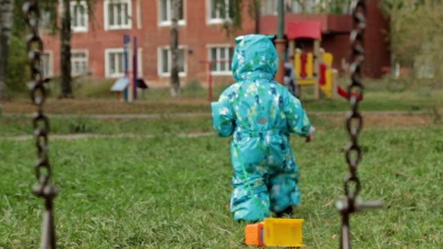 Little baby boy walking away in playground video