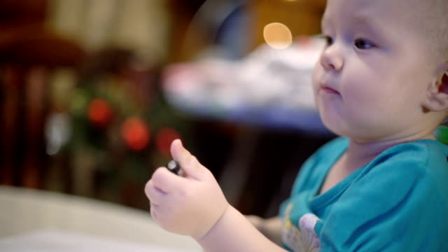 Little baby girl playing with pen and paper. Blurred Christmas lights on background video