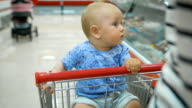 Little baby sitting in a grocery cart in a supermarket, while his father chooses purchases video