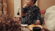 Little baby sitting on the table and eating biscuit video