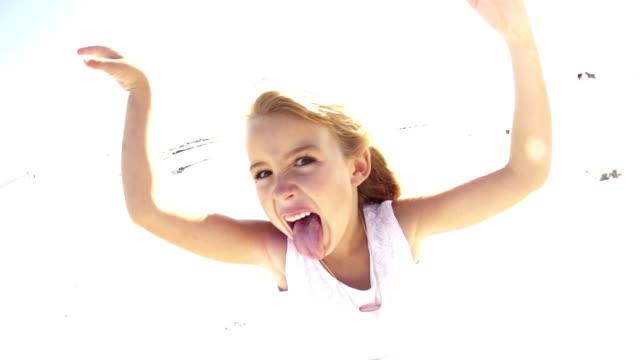 Little beach girl sticking tongue out video
