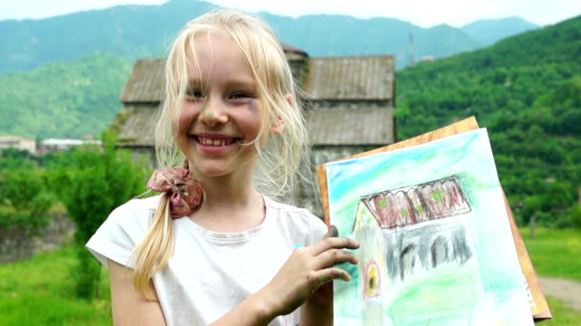 Little blonde girl showing her drawing in historical place video