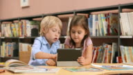 DS Little boy and a girl using a tablet in the library video