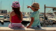 Little boy and girl sitting on a pier Yacht Club video