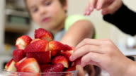 Little boy and his sister piling strawberries video