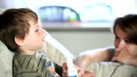 Little boy and mother using nebulizer to inhale medicine video