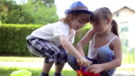 Little boy and toddler girl playing in the garden video