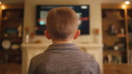 Little boy at home controlling the television, view from behind video