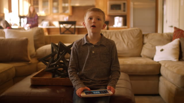 Little boy at home controlling the television with a tablet video