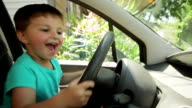 Little boy at the wheel in the car video