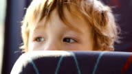 Little boy behind seat in the bus video