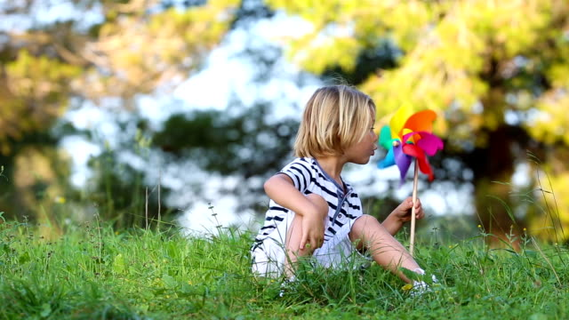 little boy blowing colored pinwheel video