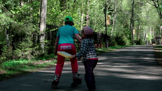 A little boy catches the girl who rides on roller skates. Slow-mo video