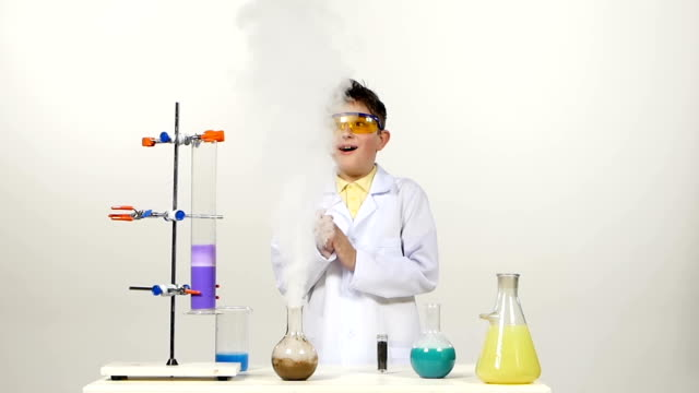 Little boy chemist in uniform, protective glasses has successfully tested the new formula, gets happy and wonders, on white background video