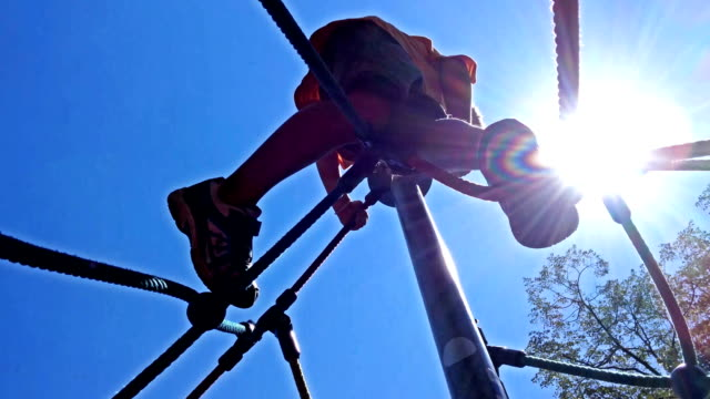 Little boy climbing on ropes with sun behind video