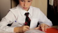 Little boy close-up of a schoolboy in a white shirt and tie is sitting at a table and writes in a notebook pen video