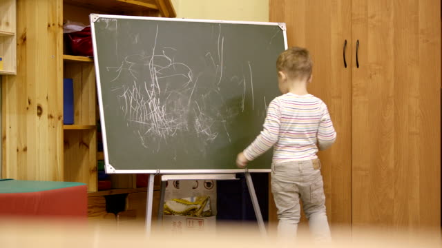 Little boy drawing on a chalkboard at kindergarten video