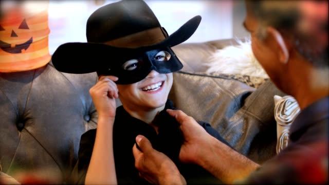 Little boy dresses up for Halloween with dad's help. video