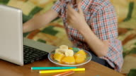 little boy eating fruit dessert and playing on laptop video
