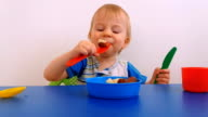 Little boy eating fruits from toy dishes video