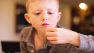 A little boy eating grapes out of a bowl in the kitchen, close up video