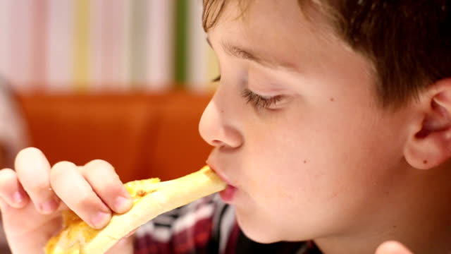 Little boy eating pizza close-up video